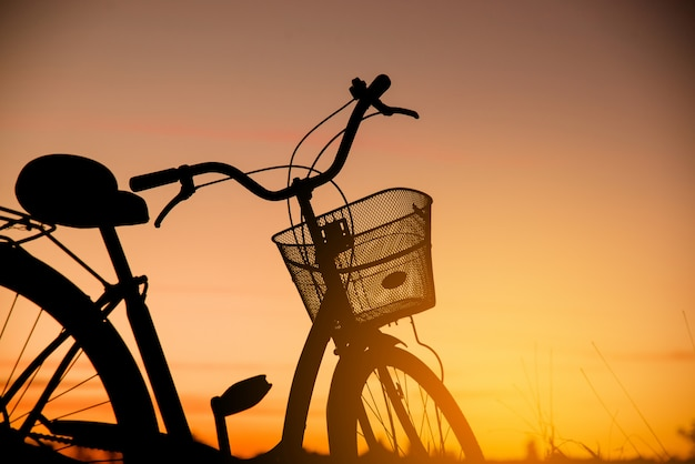 Silhouette de vélo vintage au coucher du soleil Photo gratuit