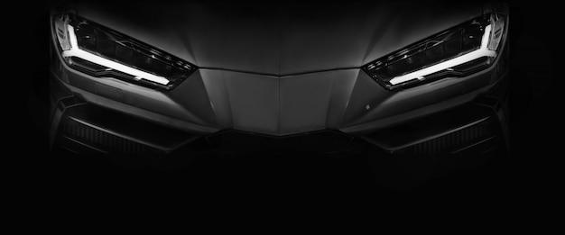 Silhouette de voiture de sport noire avec phares à led sur fond noir Photo Premium