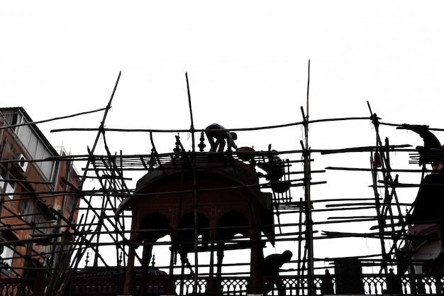 Silhouette de woker sur un échafaudage en bambou travaillant sur un chantier de construction. Photo Premium