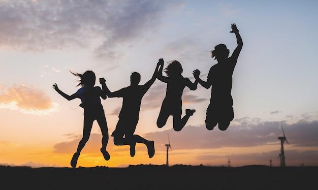 Silhouettes d'amis heureux sautant sur le coucher du soleil Photo gratuit