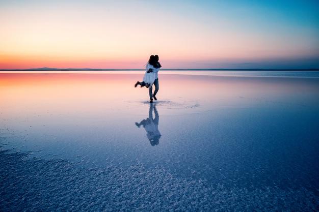 Silhouettes de câlins amoureux heureux au milieu des eaux peu profondes Photo Premium