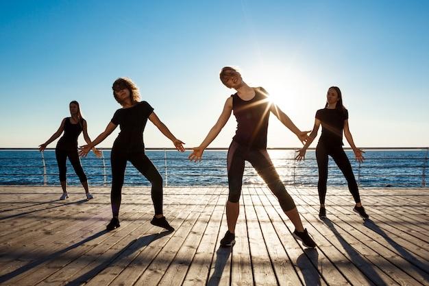 Silhouettes De Femmes Sportives Dansant Près De La Mer Au Lever Du Soleil Photo gratuit