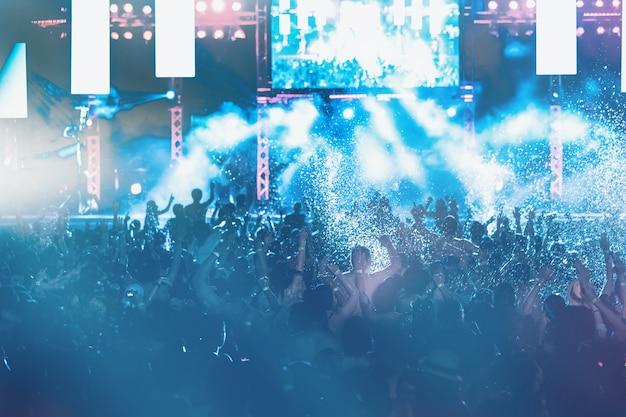 Silhouettes de la foule en concert devant les lumières de la scène, fête au bord de la piscine Photo Premium