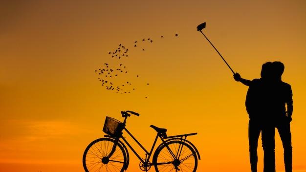 Silhouettes homme et femme prenant selfie avec smartphone sur ciel coucher de soleil: photo de la silhouette. Photo Premium