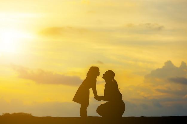 Silhouettes De Mère Et Fille Jouant Au Coucher Du Soleil Photo Premium