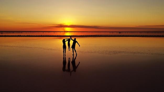 Silhouettes De Trois, Papa, Maman Et Petite Fille Marchant Dans Les Bas-fonds D'un Lac Photo Premium