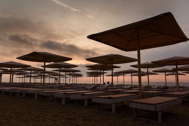 Silhuettes de transats et parasols sur une plage déserte le soir Photo Premium