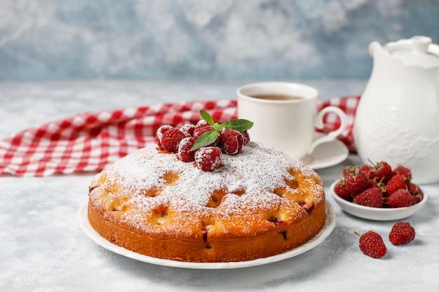 Simple gâteau avec du sucre en poudre et des framboises fraîches sur une lumière. dessert aux baies d'été. Photo gratuit