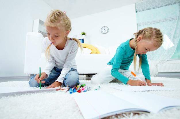 Sisters Assis Sur La Peinture à L'étage Photo gratuit