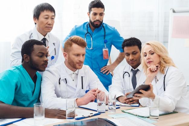 Six médecins de différents pays examinent quelque chose Photo Premium