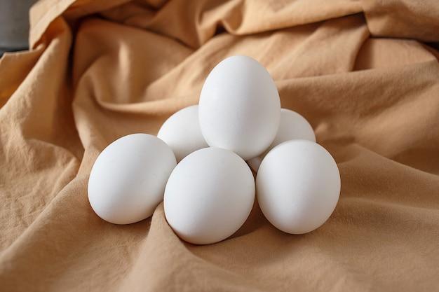 Six oeufs de poule blancs sur fond beige Photo Premium