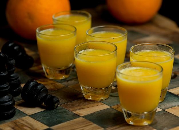 Six petits verres de jus d'orange frais sur un tableau d'affichage Photo gratuit