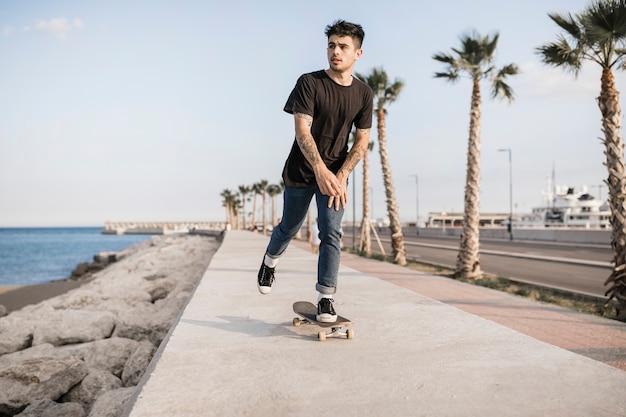 Skateboard attrayant adolescent près de la côte Photo gratuit