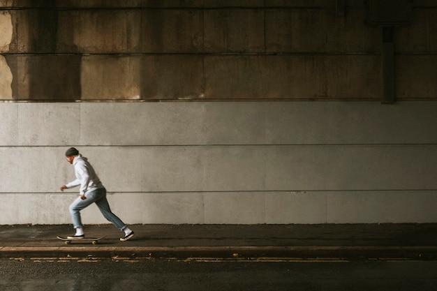 Skateboarding Homme Sous Un Pont Avec Espace De Conception De Mur Urbain Photo gratuit