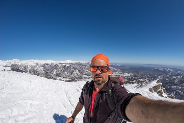 Skieur alpin adulte avec barbe, lunettes de soleil et chapeau, prenant selfie sur une pente enneigée dans les magnifiques alpes italiennes avec un ciel bleu clair. image tonique, style vintage, objectif ultra grand angle fisheye. Photo Premium