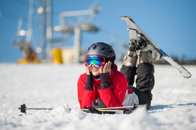 Skieur femme couchée avec des skis sur la neige au sommet de la montagne Photo Premium