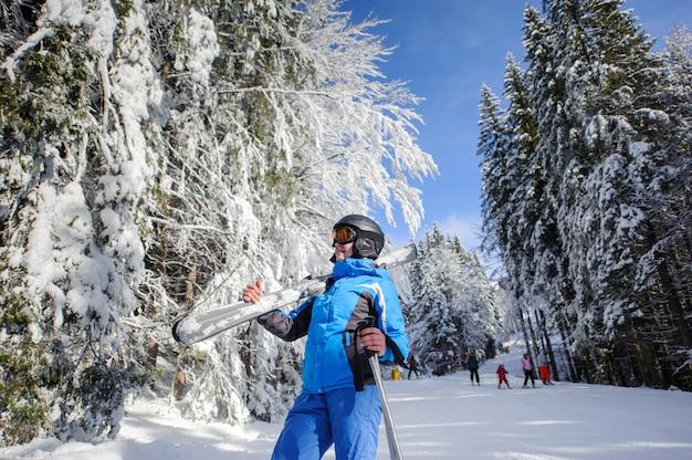 Skieuse sur une piste de ski dans la forêt en hiver par une journée ensoleillée Photo Premium