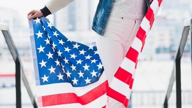Slim femme tenant un drapeau américain derrière les jambes Photo gratuit