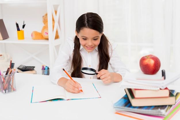 Smart écolière hispanique lisant à travers la loupe Photo gratuit
