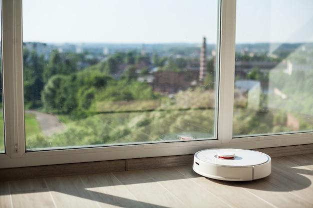 Smart house, robot aspirateur fonctionne sur un plancher de bois dans un salon Photo Premium