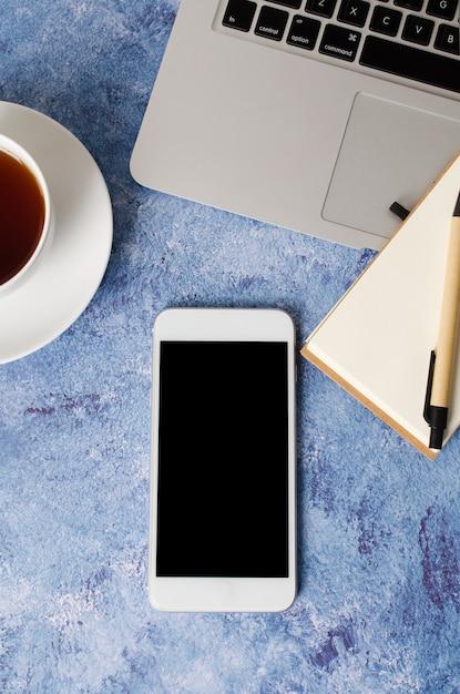 Smartphone Blanc Avec écran Blanc Noir Sur Le Bureau Avec Ordinateur Portable, Ordinateur Portable Vide Et Tasse De Thé. Maquette De Téléphone. Photo Premium
