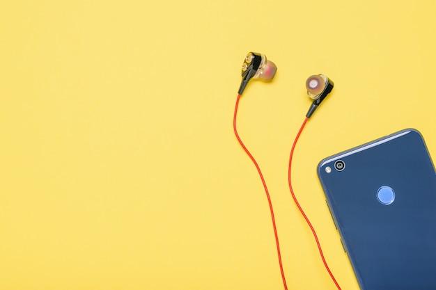 Smartphone bleu avec un casque rouge sur fond jaune. Photo Premium