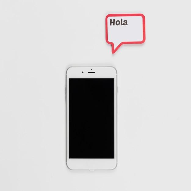 Smartphone et cadre avec inscription hola Photo gratuit