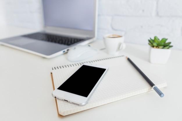 Smartphone carnet et crayon en face de l ordinateur portable sur