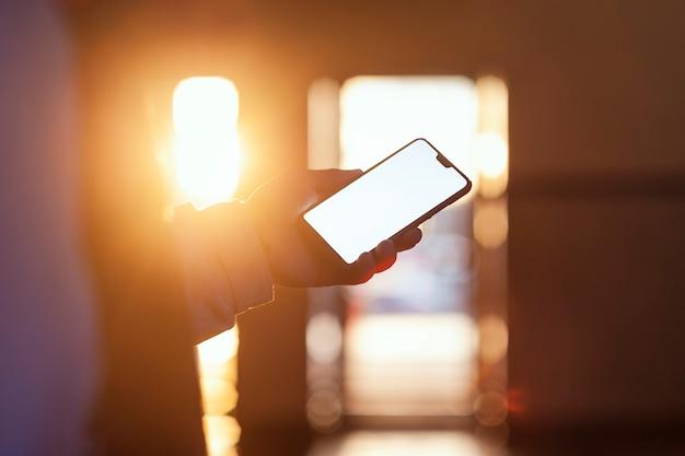 Le Smartphone Dans La Main Du Mec Contre Le Coucher De Soleil. Photo Premium