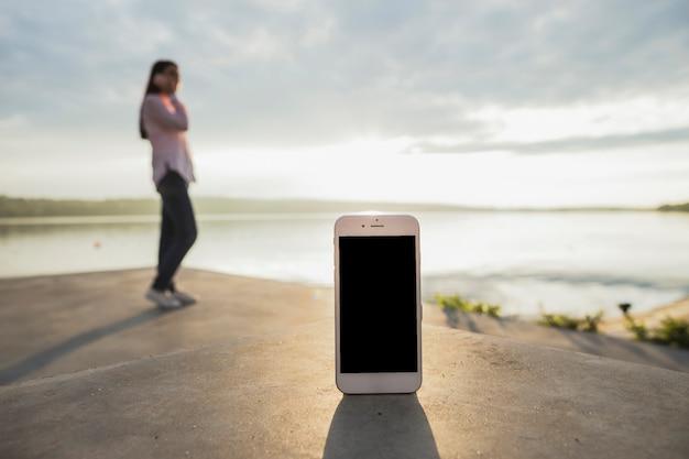 Smartphone, devant, femme, conversation, téléphone portable, debout, près, lac Photo gratuit