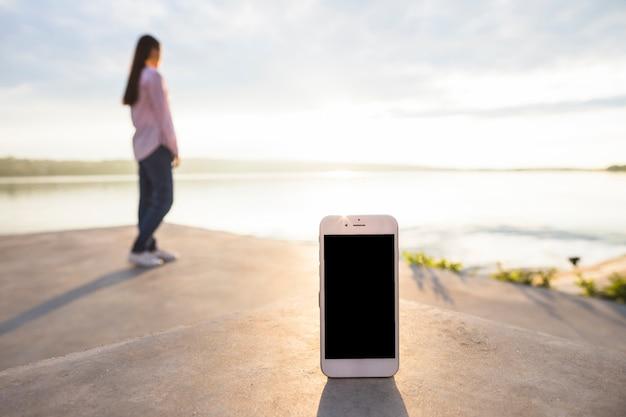 Smartphone devant une femme debout près du lac idyllique Photo gratuit