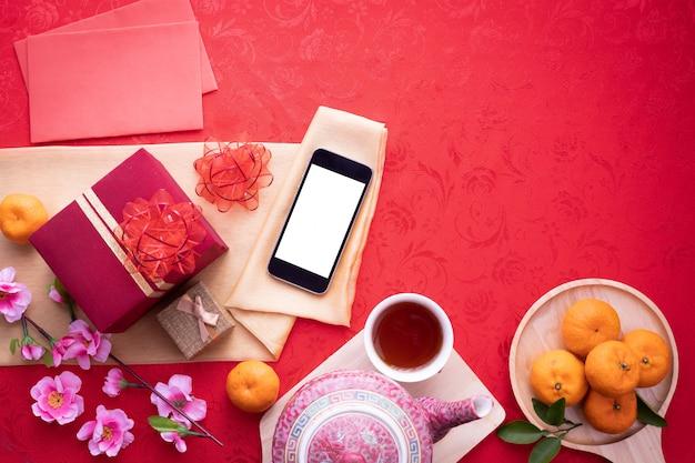 Smartphone d'écran blanc avec la composition du nouvel an chinois sur fond rouge. Photo Premium