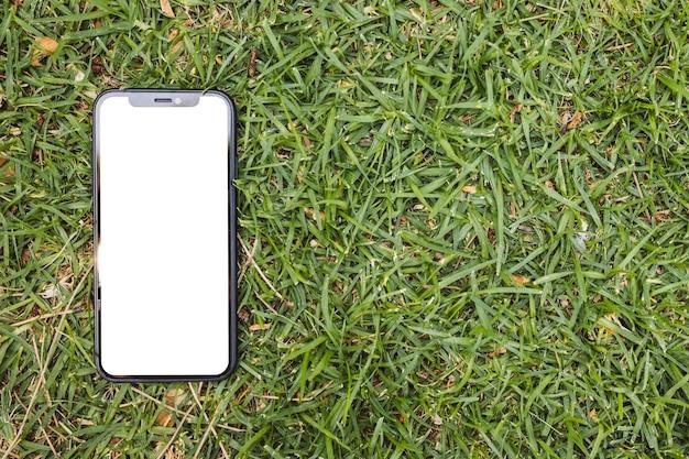 Smartphone Avec Un écran Blanc Sur L'herbe Photo gratuit