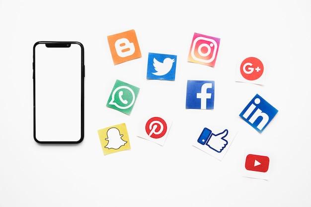 Smartphone avec écran blanc vide en plus des icônes de médias sociaux vives Photo gratuit