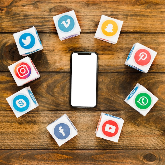 Smartphone à écran tactile entouré de boîtes d'icônes d'applications multimédia Photo gratuit