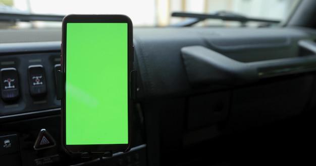 Smartphone avec un écran vert dans le support sur le pare-brise Photo Premium