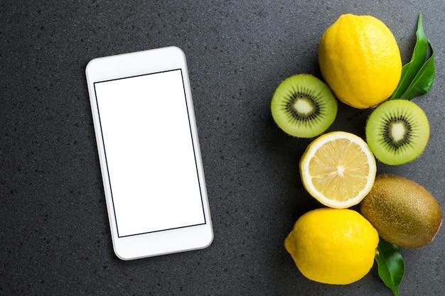 Un smartphone avec un écran vide avec des citrons et des kiwis se trouve sur la table en pierre noire. vue de dessus, plat poser. Photo Premium