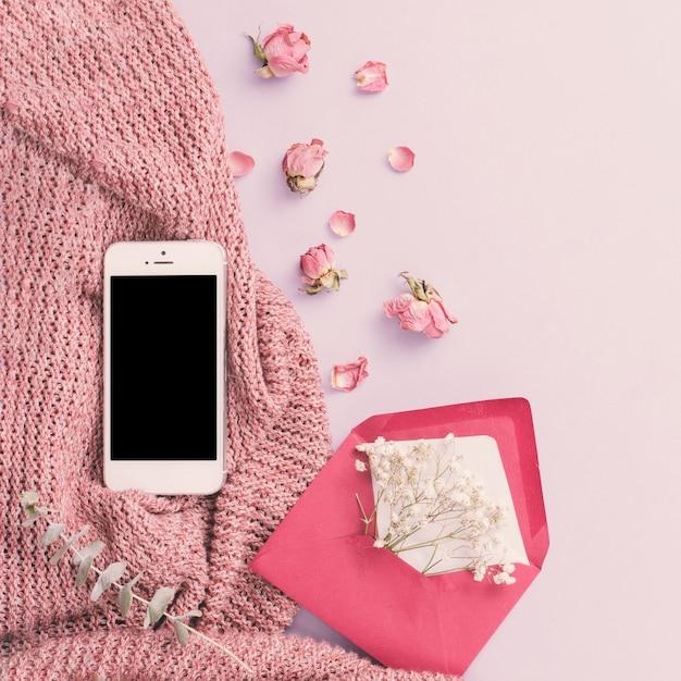 Smartphone avec des fleurs dans une enveloppe Photo gratuit