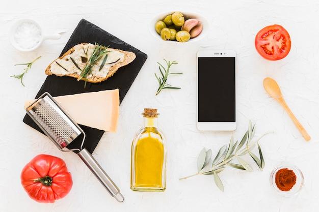 Smartphone avec fromage, pain et ingrédients sur fond blanc Photo gratuit