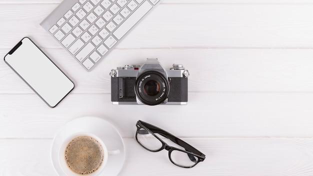 Smartphone, lunettes, appareil photo, tasse et clavier Photo gratuit
