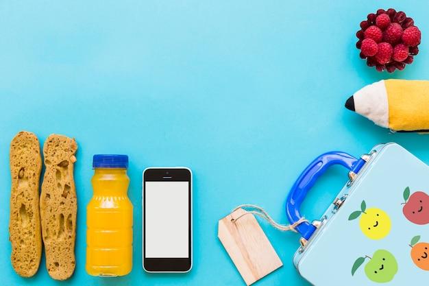 Smartphone et de la nourriture saine près de lunchbox et étui à crayons Photo gratuit