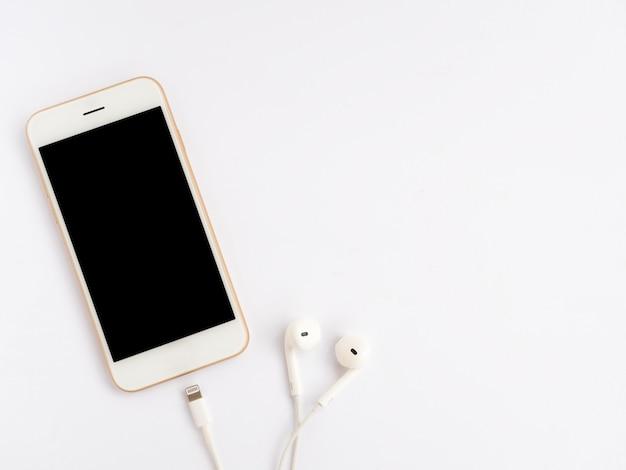 Smartphone, oreillettes et câble de charge sur blanc Photo Premium
