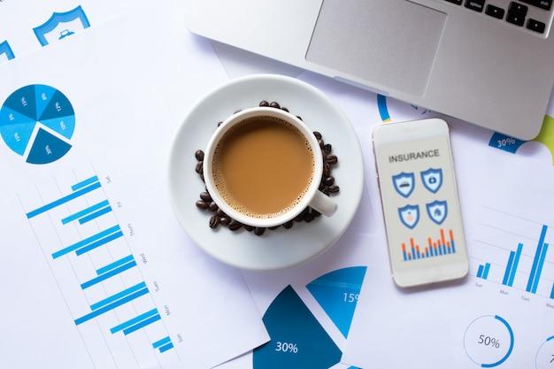 Smartphone pour rechercher une assurance en ligne et café, document, ordinateur portable sur le bureau le matin. assurance Photo Premium