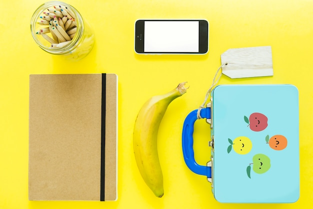 Smartphone près de la boîte à lunch et de la papeterie Photo gratuit