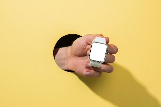 Smartwatch maquette vue de face tenue par personne Photo gratuit