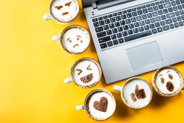 Smile emoji peint sur des tasses de cappuccino à côté de l'ordinateur portable sur un fond jaune Photo Premium