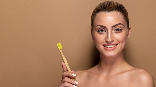 Smiley adulte femme tenant une brosse à dents Photo gratuit
