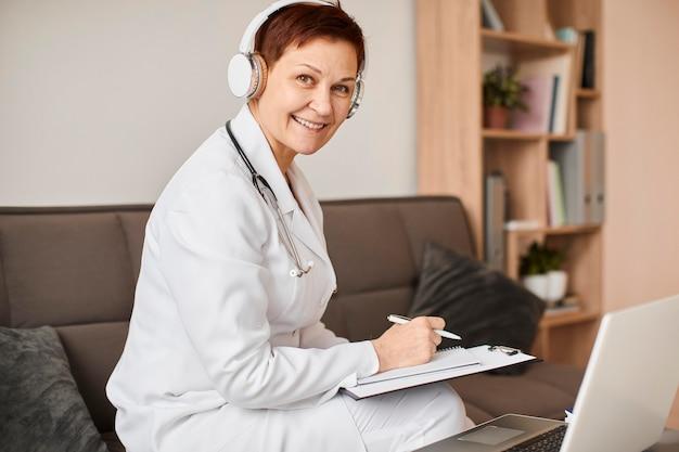 Smiley Aîné Centre De Récupération De Covid Femme Médecin Avec écouteurs Et Presse-papiers Photo gratuit