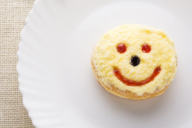 Smiley beignet sur une assiette, beignet Photo Premium