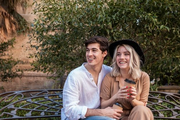 Smiley Couple Sur Banc Au Parc Photo gratuit